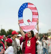 En man håller upp ett skylt med ett Q för Qanon under ett Trump-rally 2018.  Matt Rourke / TT NYHETSBYRÅN