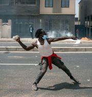En demonstrant som kastar sten. Leo Correa / TT NYHETSBYRÅN