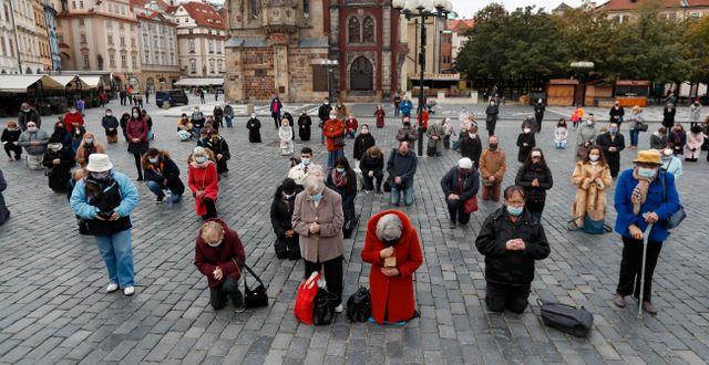 Människor ber på ett torg i Prag Petr David Josek / TT NYHETSBYRÅN