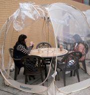 Två kvinnor sitter och fikar i ett plasttält i New Jersey.  Seth Wenig / TT NYHETSBYRÅN