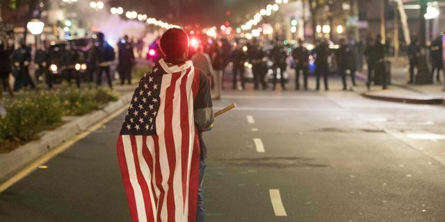 En demonstrant bär på den amerikanska flaggan. I bakgrunden syns kravallpolis. JOSH EDELSON / AFP