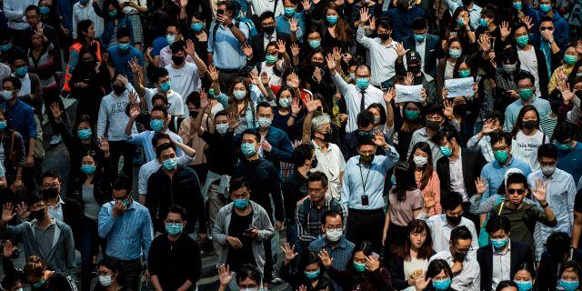 Kontorsarbetare demonstrerar och visar sitt stöd för Hongkong-protesterna på lunchrasten. ISAAC LAWRENCE / AFP