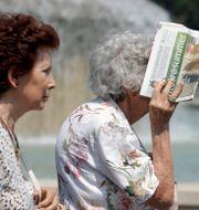 Äldre kvinna i Milano i Italien skyddar ansiktet mot hettan med en tidning. Illustrationsbild. Luca Bruno / TT NYHETSBYRÅN