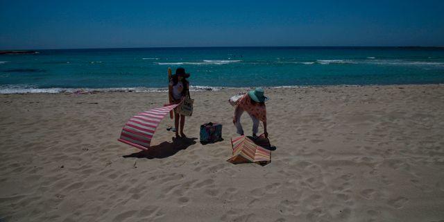 Solbadare på en tom strand i Ayia Napa. Petros Karadjias / TT NYHETSBYRÅN