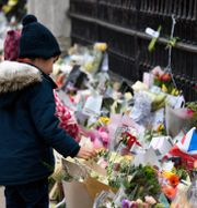 Barn tittar på blommor utanför Buckingham Palace. Alberto Pezzali / TT NYHETSBYRÅN