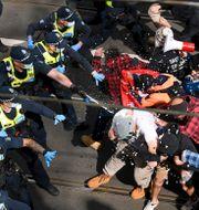 Polisen sprejar tårgas mot demonstranter på lördagen. James Ross / TT NYHETSBYRÅN