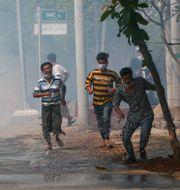 Demonstranter springer från polisen i Mandalay i Myanmar.  STR / TT NYHETSBYRÅN