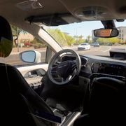 A Waymo minivan moves along a city street as an empty driver's seat and a moving steering wheel drive passengers during an autonomous vehicle ride, Wednesday, April 7, 2021, in Chandler, Ariz. Waymo, a unit of Google parent Alphabet Inc., is one of several companies testing driverless vehicles in the U.S. But it's the first offering lifts to the public with no humans at the wheel who can take over in sticky situations. Ross D. Franklin / TT NYHETSBYRÅN