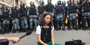 """En demonstrant ur gruppen """"Bessrochka"""" sitter framför rysk polis under en protest, 27 juli. Alexei Abanin / TT NYHETSBYRÅN"""