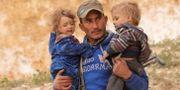 SDF-medlem bär två barn i staden Baghuz. Issam Abdallah / TT NYHETSBYRÅN