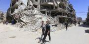 Människor ses vandra i Douma under ett organiserat besök för journalister under måndagen. LOUAI BESHARA / AFP