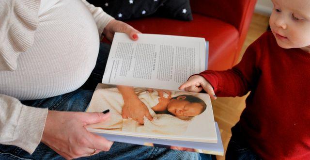 Illustrationsbild. En gravid kvinna läser en bok om spädbarn. JESSICA GOW / TT / TT NYHETSBYRÅN