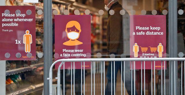 Uppmaningar om att hålla avstånd vid en butik. Alastair Grant / TT NYHETSBYRÅN