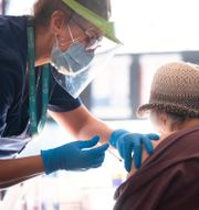 En äldre dam i hatt blir vaccinerad mot covid-19. Fredrik Sandberg/TT / TT NYHETSBYRÅN