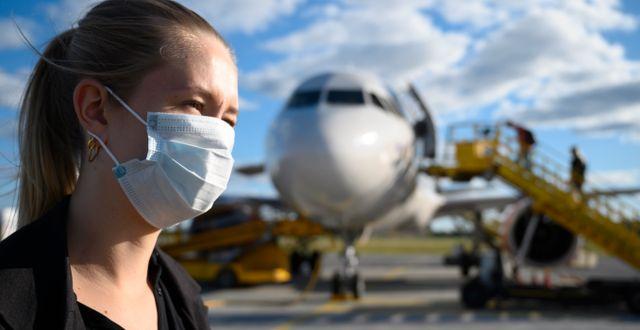 Illustrationsbild, kvinna med munskydd framför flygplan. Henrik Montgomery/TT / TT NYHETSBYRÅN