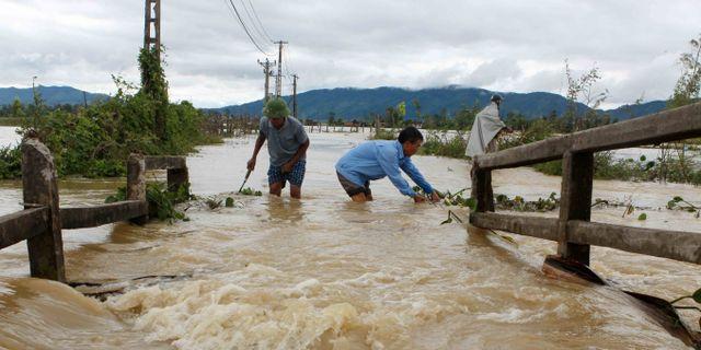 Män vadar i ett översvämmat område i Nghe An.  VIETNAM NEWS AGENCY / Vietnam News Agency