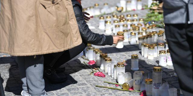 En person tänder ljus vid en minnesplats för de tre personer som dödats i skjutningar i Sätra i Stockholm. Fredrik Sandberg/TT / TT NYHETSBYRÅN