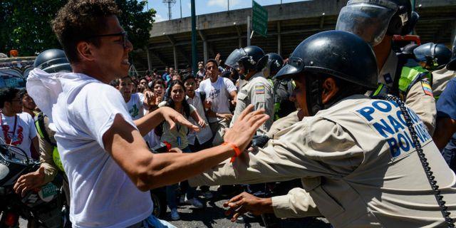 En demonstrant knuffas bort av en polis vid en demonstration i Caracas den 15 februari. FEDERICO PARRA / AFP