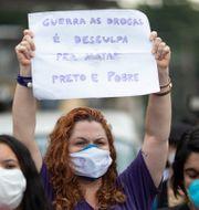 """Kvinna i Rio de Janeiro. Skylt med texten: """"Kriget mot drogerna är en ursäkt för att döda svarta och fattiga"""".  Silvia Izquierdo / TT NYHETSBYRÅN"""