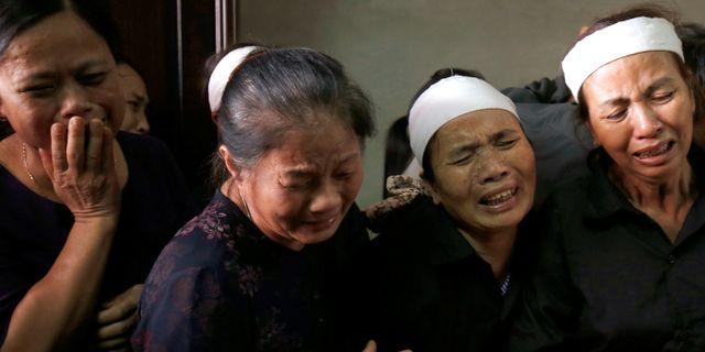 Anhöriga sörjer på begravningen av en journalist som dog i översvämningarna.  KHAM / TT NYHETSBYRÅN