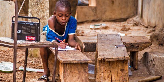 En pojke i Sierra Leone lyssnar på lektioner över radion under ebolakrisen 2015. Michael Duff / TT NYHETSBYRÅN