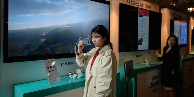 En kvinna tittar på en Samsungtelefon i Seoul på fredagen.  ED JONES / AFP