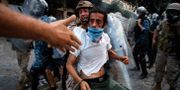 Demonstrant och polis i Beirut. Thibault Camus / TT NYHETSBYRÅN
