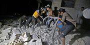 Personer ur de så kallade Vita hjälmarna arbetar efter ett luftangrepp i Idlib i torsdags. ABDULAZIZ KETAZ / AFP