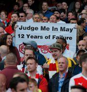 Arsenalfans som är kritiska till Arsene Wenger håller upp en banderoll som anspelar på att Arsenal inte vunnit en titel på tolv år. Andrew Couldridge / TT NYHETSBYRÅN