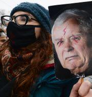 Demonstrant håller upp en bild på Lag och rättvisas ledare Jaroslaw Kaczynski.  Czarek Sokolowski / TT NYHETSBYRÅN