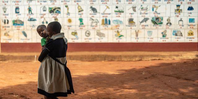 En flicka bär sitt syskon.  ZINYANGE AUNTONY / AFP