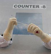Vårpersonal i Indien bakom ett skydd sträcker fram händerna genom två hål för att coronatesta med en tops.  Mahesh Kumar A / TT NYHETSBYRÅN