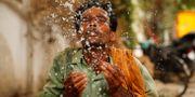 En man svalkar sig med lite vatten i hettan. Rajesh Kumar Singh / TT NYHETSBYRÅN