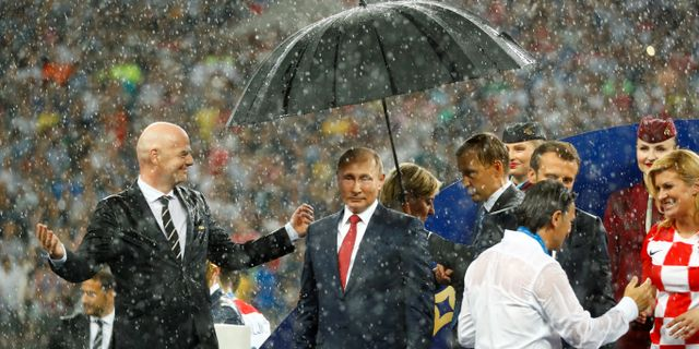 Vladimir Putin med paraply över huvudet. Till vänster Fifapresident Gianni Infantino och till höger Emmanuel Macron och Kolinda Grabar-Kitarovic. KAI PFAFFENBACH / TT NYHETSBYRÅN