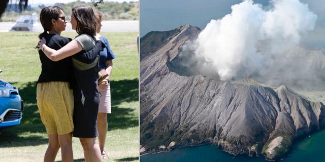 Två kvinnor kramar om varandra efter att ha lagt blommor på en minnesplats för offren efter Vulkanutbrottet i Nya Zeeland.  TT