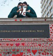 Sjuksköterskor från St Thomas sjukhus i London sitter på en minnesplats för människor som dött med covid-19. Frank Augstein / TT NYHETSBYRÅN