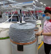 Kvinna på bomullsfabrik i Xinjiangprovinsen under ett besök av journalister arrangerat av kinesiska staten.  Mark Schiefelbein / TT NYHETSBYRÅN