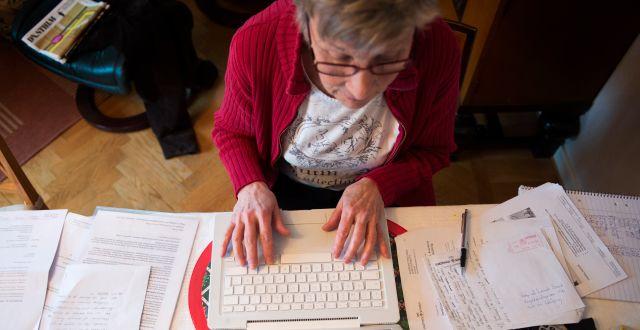 En kvinnlig pensionär sitter vid en bärbar dator och skriver. FREDRIK SANDBERG / TT / TT NYHETSBYRÅN