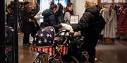 Illustration: Kinesisk man med barnvagn i USA:S färger i Peking. Andy Wong / TT NYHETSBYRÅN/ NTB Scanpix