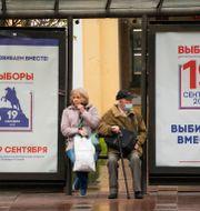 Människor på en busshållplats i St Petersburg, som dekorerats med valaffischer.  Dmitri Lovetsky / TT NYHETSBYRÅN