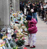 Människor lägger blommor utanför Buckingham Palace.  Alberto Pezzali / TT NYHETSBYRÅN