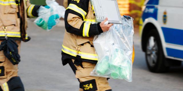 Räddningstjänstpersonal bär ut föremål i plastpåsar från en förskola i Gustavsberg där man hittat giftampuller Fredrik Persson / TT Nyhetsbyrån