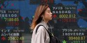 En kvinna passerar skyltar med börsinformation vid ett finanshus i Tokyo på tisdagen  Koji Sasahara / TT NYHETSBYRÅN