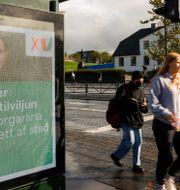 Väljare går förbi en valaffisch med premiärminister Katrín Jakobsdóttir i Reykjavik. Brynjar Gunnarsson / TT NYHETSBYRÅN
