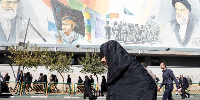 En kvinna går framför en väggmålning i Teheran.  STR / afp