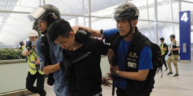 Poliser griper demonstrant på flygplatsen, 13 augusti Kin Cheung / TT NYHETSBYRÅN/ NTB Scanpix