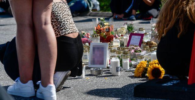 Folk samlas vid blommorna och ljusen på platsen där en tolvårig flicka sköts ihjäl Stina Stjernkvist/TT / TT NYHETSBYRÅN