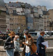 Personer på väg över n bro i Paris.  Michel Euler / TT NYHETSBYRÅN