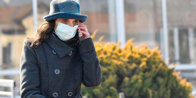 Kvinna med ansiktsmask lämnar sjukhuset i italienska Codogno.  FLAVIO LO SCALZO / TT NYHETSBYRÅN