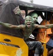 Anhängare av presidenten firar segern. Sunday Alamba / TT NYHETSBYRÅN